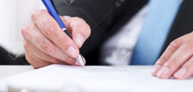 14351892-businessman-sitting-at-office-desk-signing-a-contract-with-focus-on-signature-stock-photo